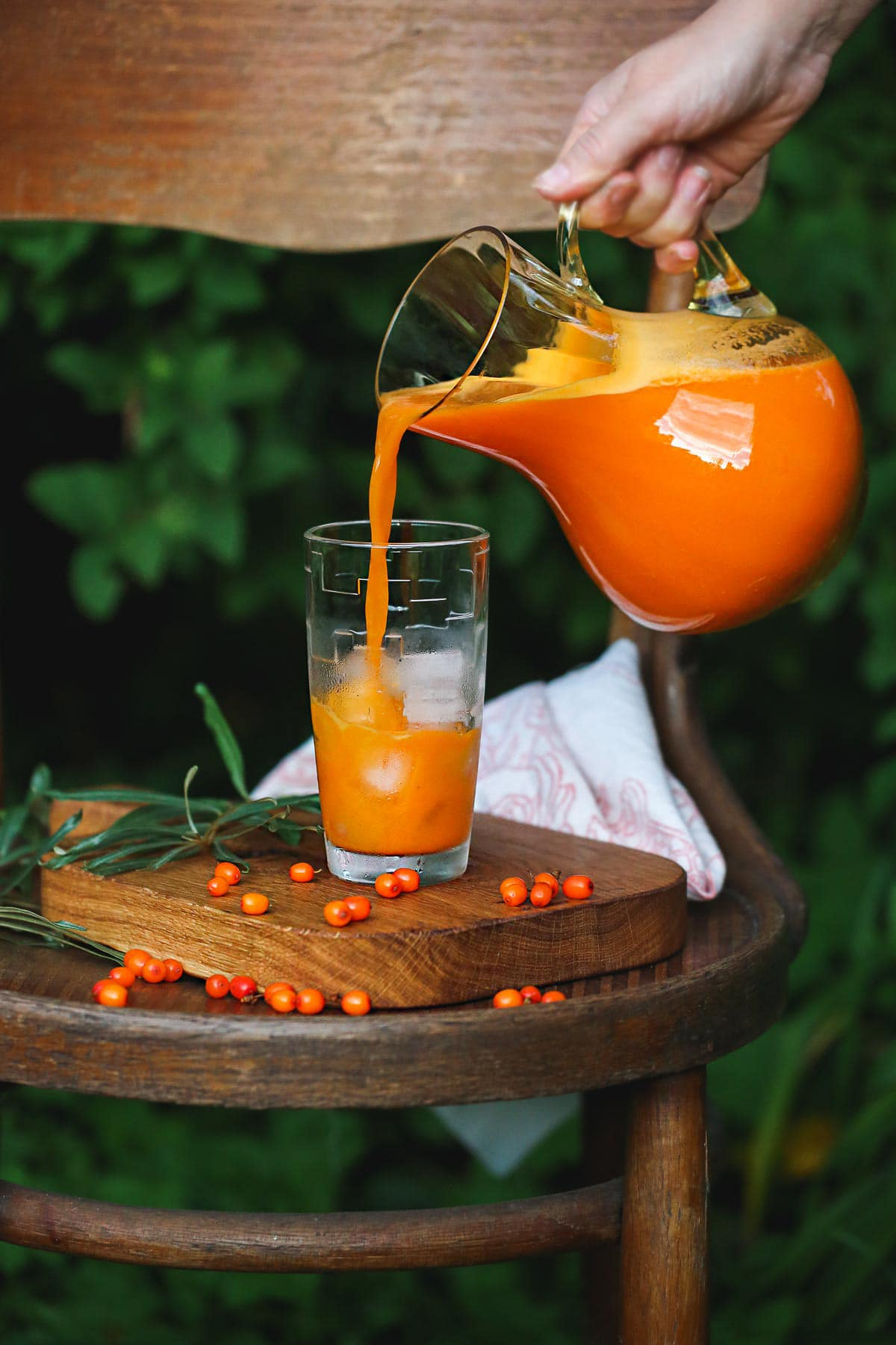 Pouring sea buckthorn juice from a jug into a glass placed on a wooden board