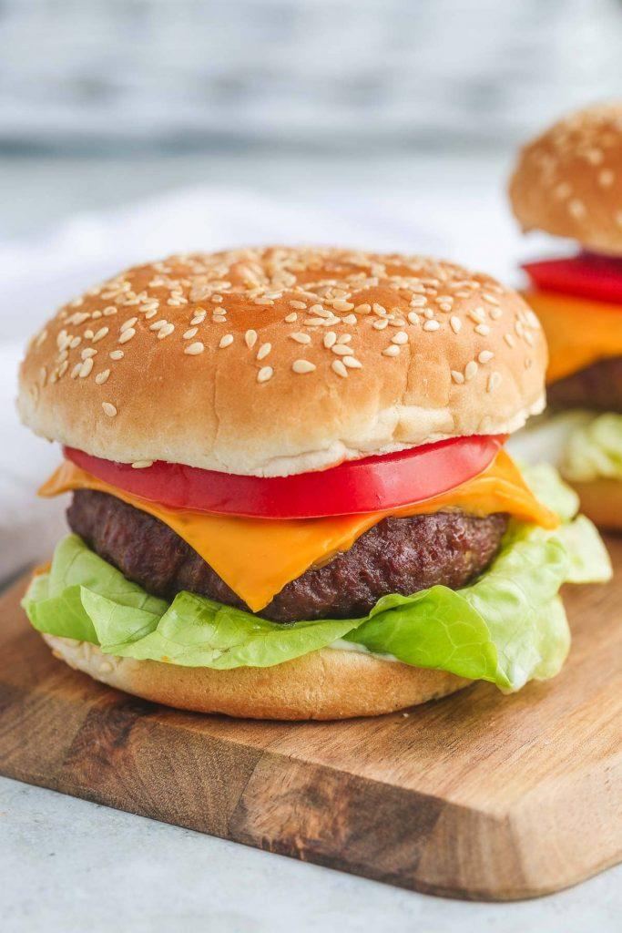 a juicy hamburger in a bin on a wooden board