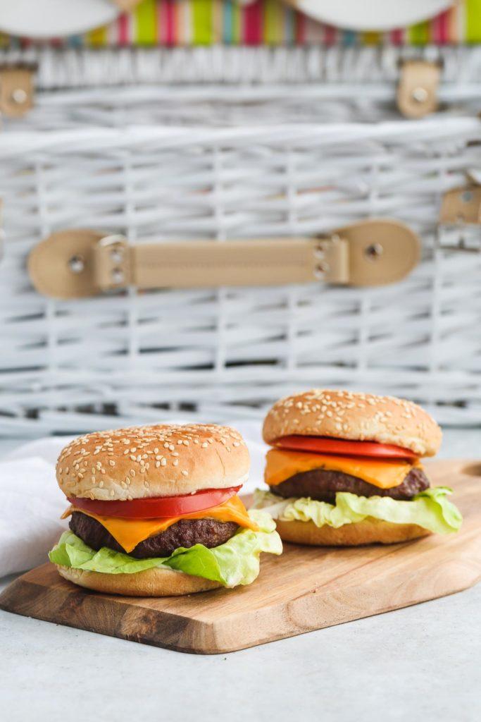 2 hamburgers on a wooden board