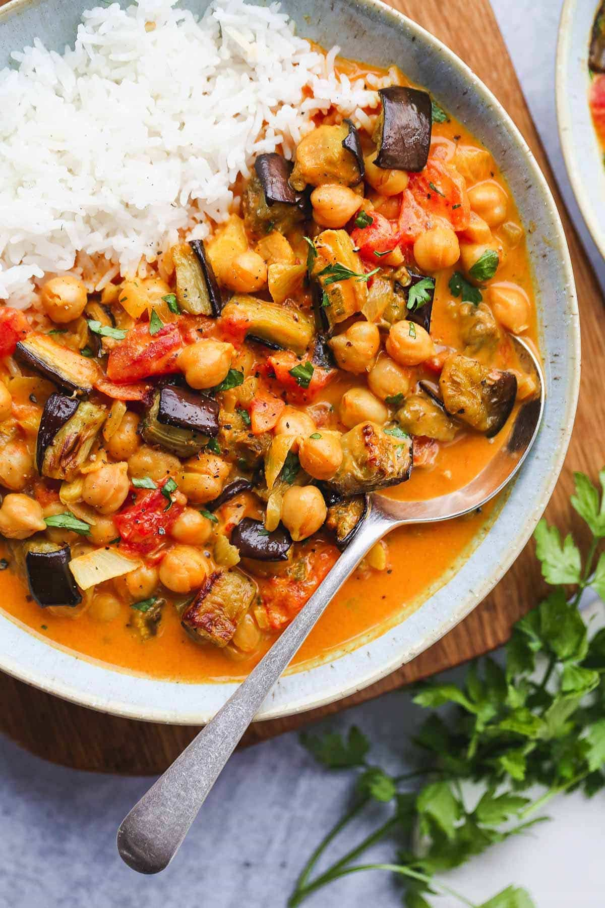 A close up shot of aubergine and Chickpea Curry with white basmati rice in a bowl with a spoon