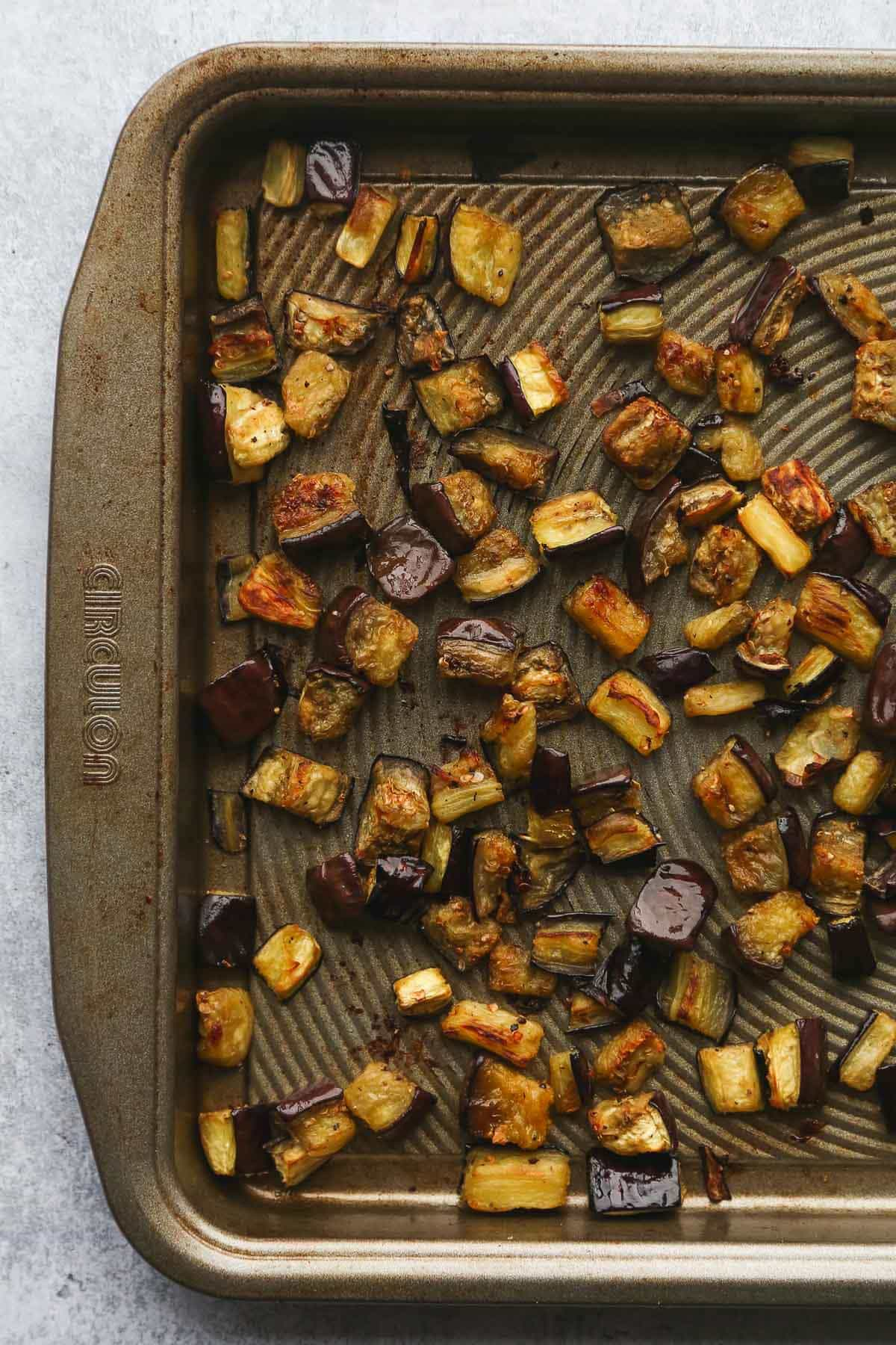 Roasted aubergine cubes on a roasting pan.