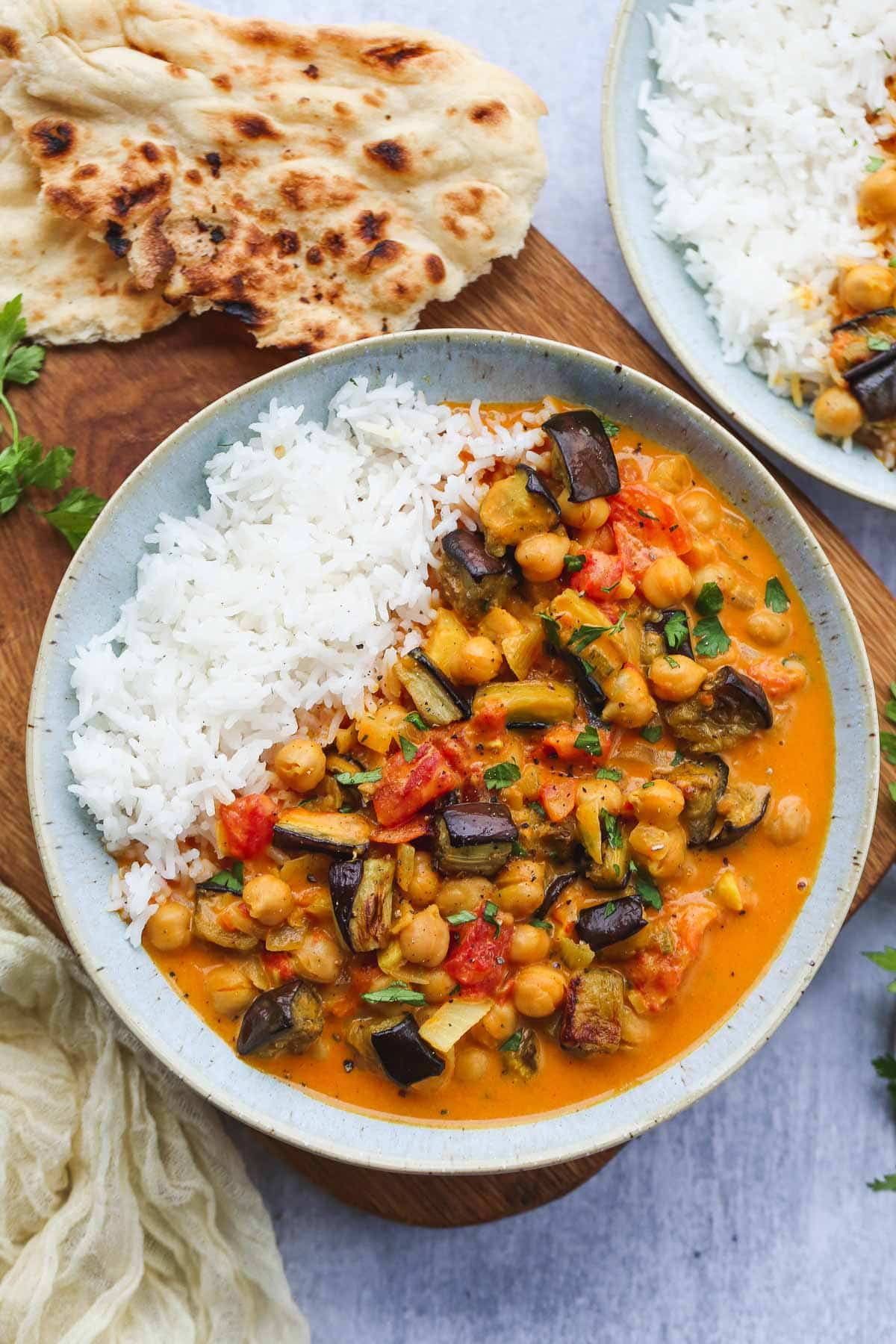 Aubergine and Chickpea Curry bowl with white rice on a wooden word served with naan bread