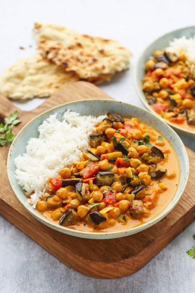 A bowl of Aubergine and Chickpea Curry served with white basmati rice over a wooden board