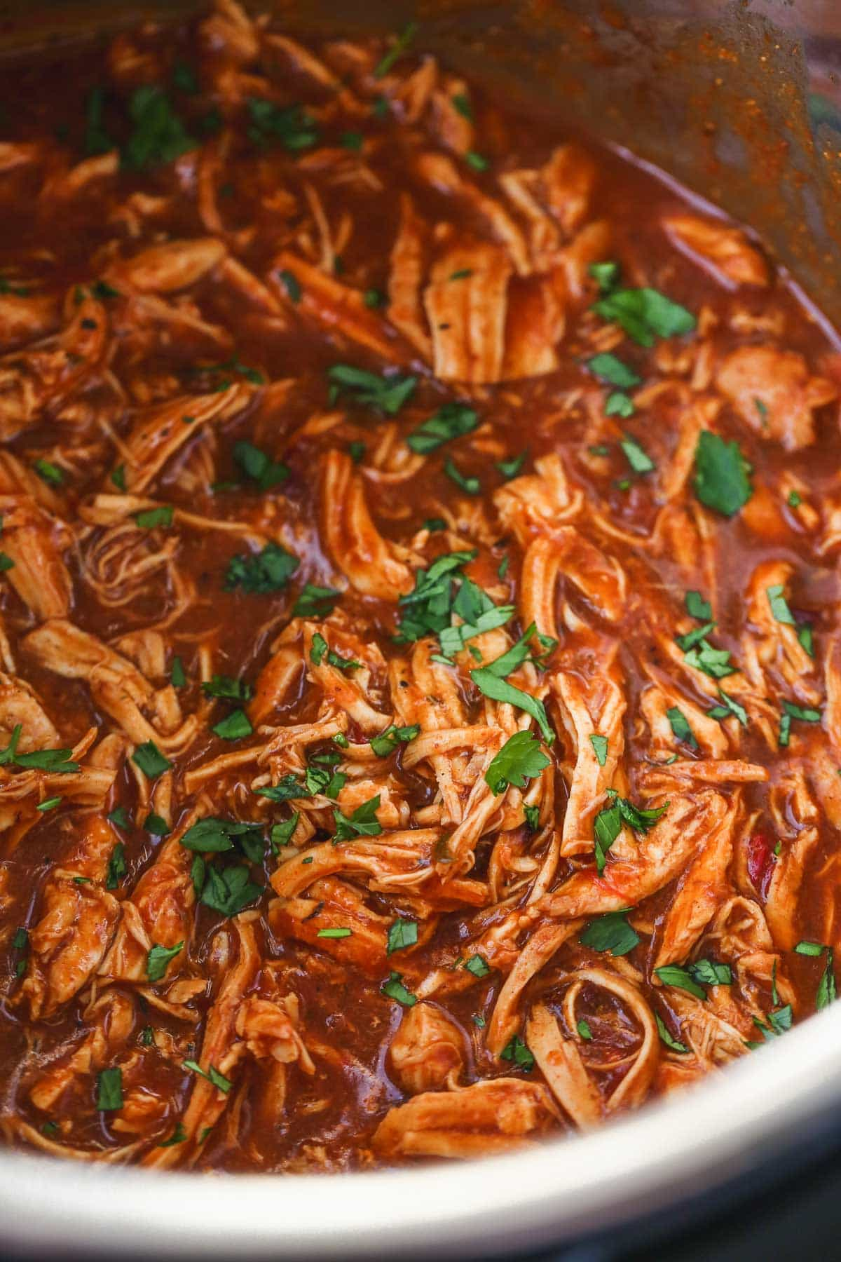 Shredded salsa chicken inside the Instant Pot, garnished with chopped parsley