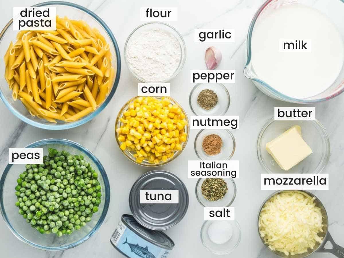 Ingredients needed to make tuna casserole including pasta, peas, corn, tuna, milk, butter, cheese, garlic, and seasonings.