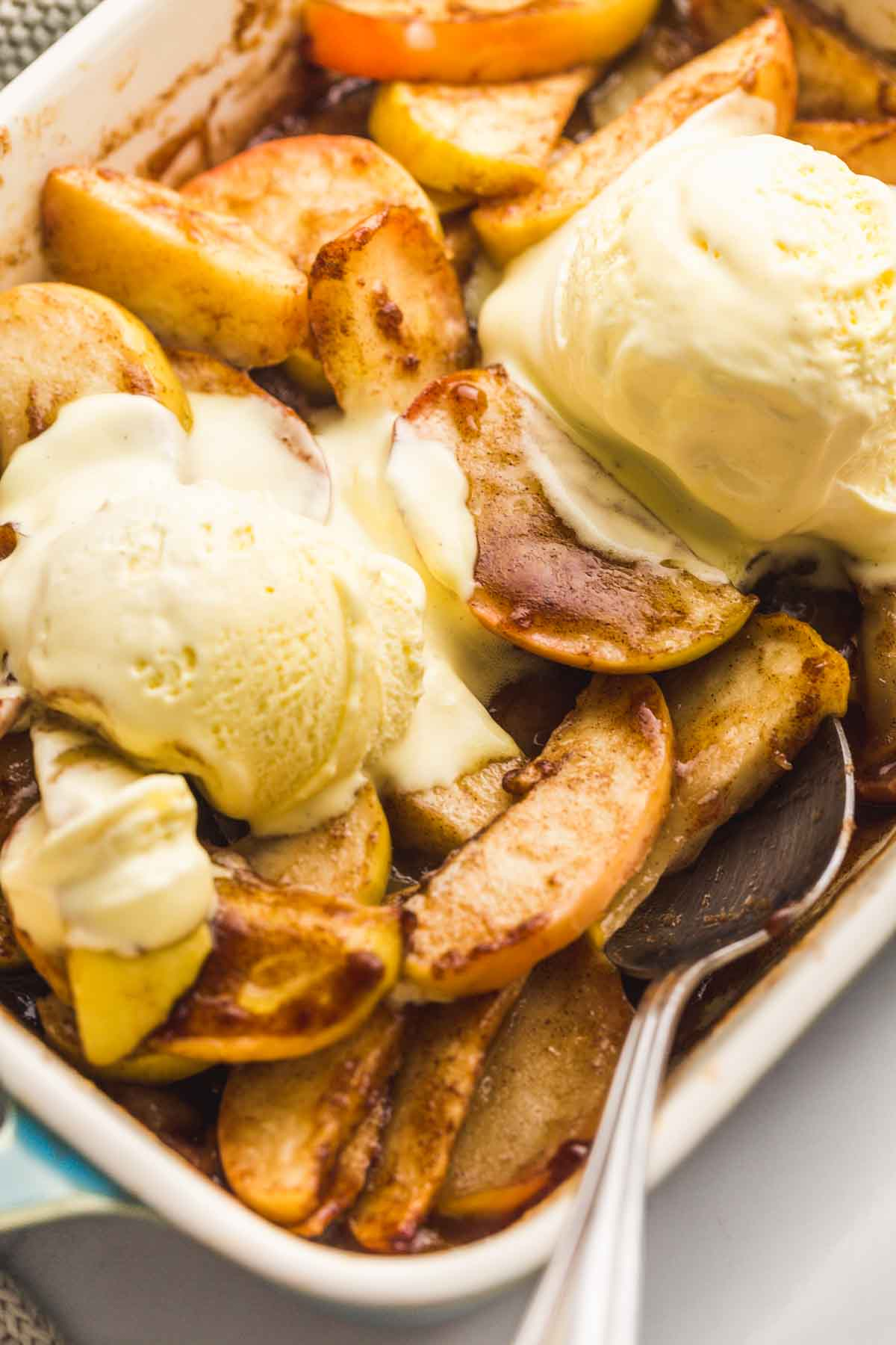 A close up of baked apples, and vanilla ice cream scoops