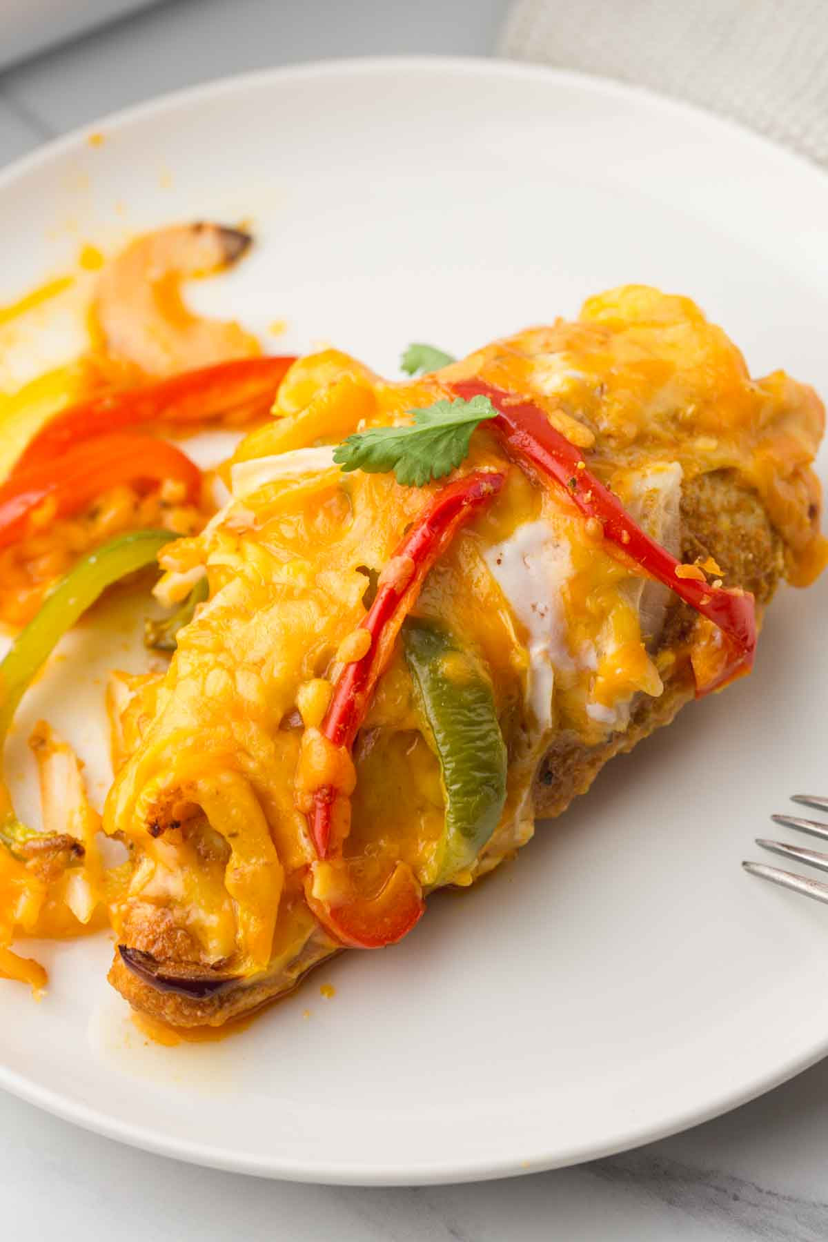 Chicken breast with fajita bell peppers and cheese, served in a white plate
