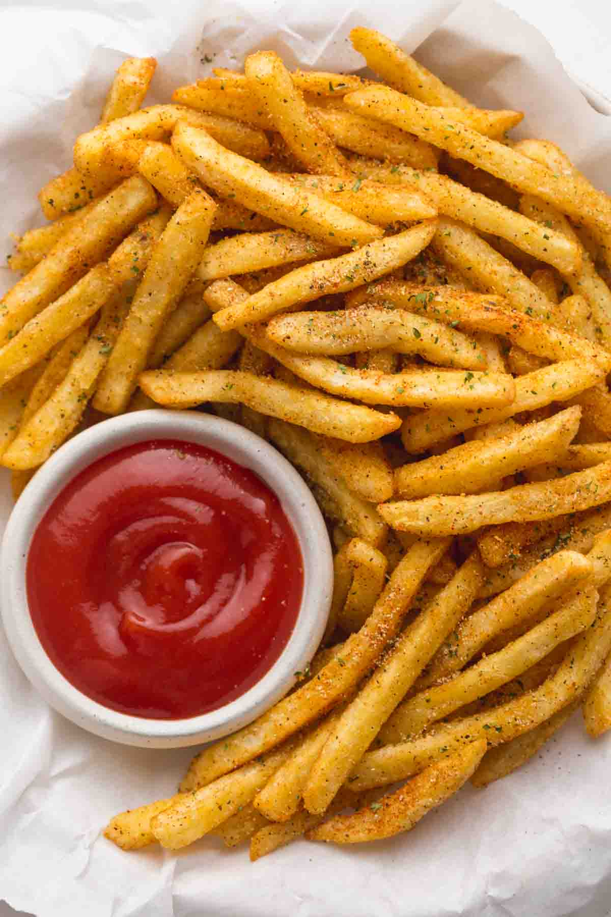 Close up of golden french fries with French Fry Seasoning and ketchup