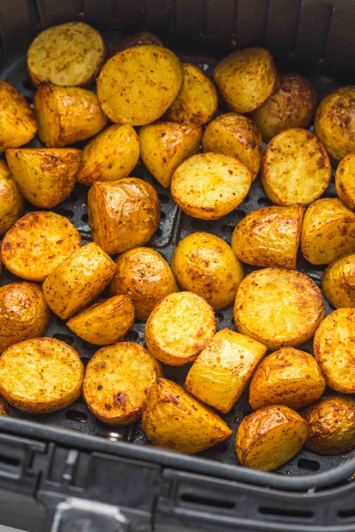 A close up of roasted potatoes in the air fryer basket