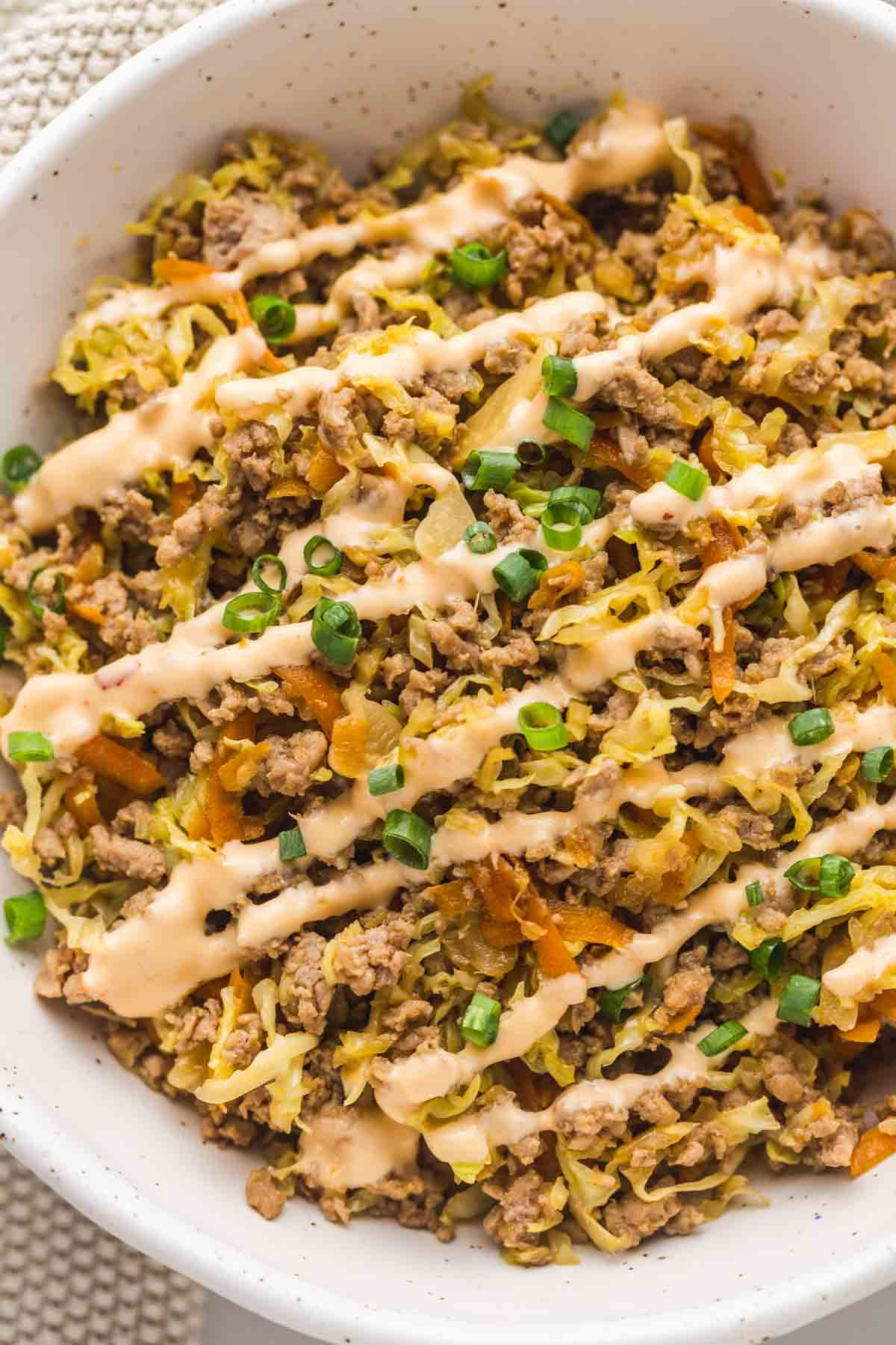 A close up of Egg Roll in a Bowl with creamy chili mayo drizzle