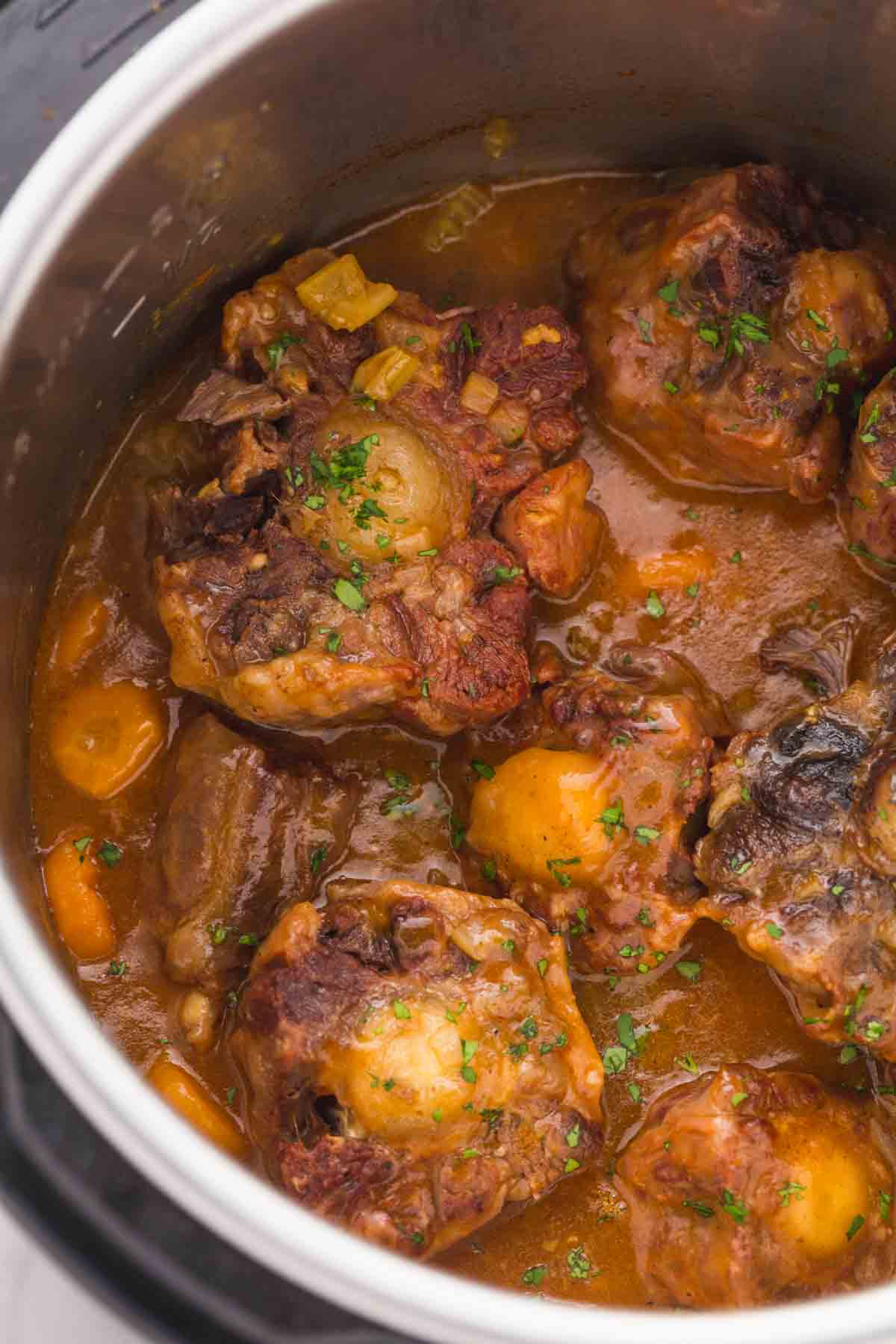 Cooked oxtails in the instant pot with a rich sauce and vegetables