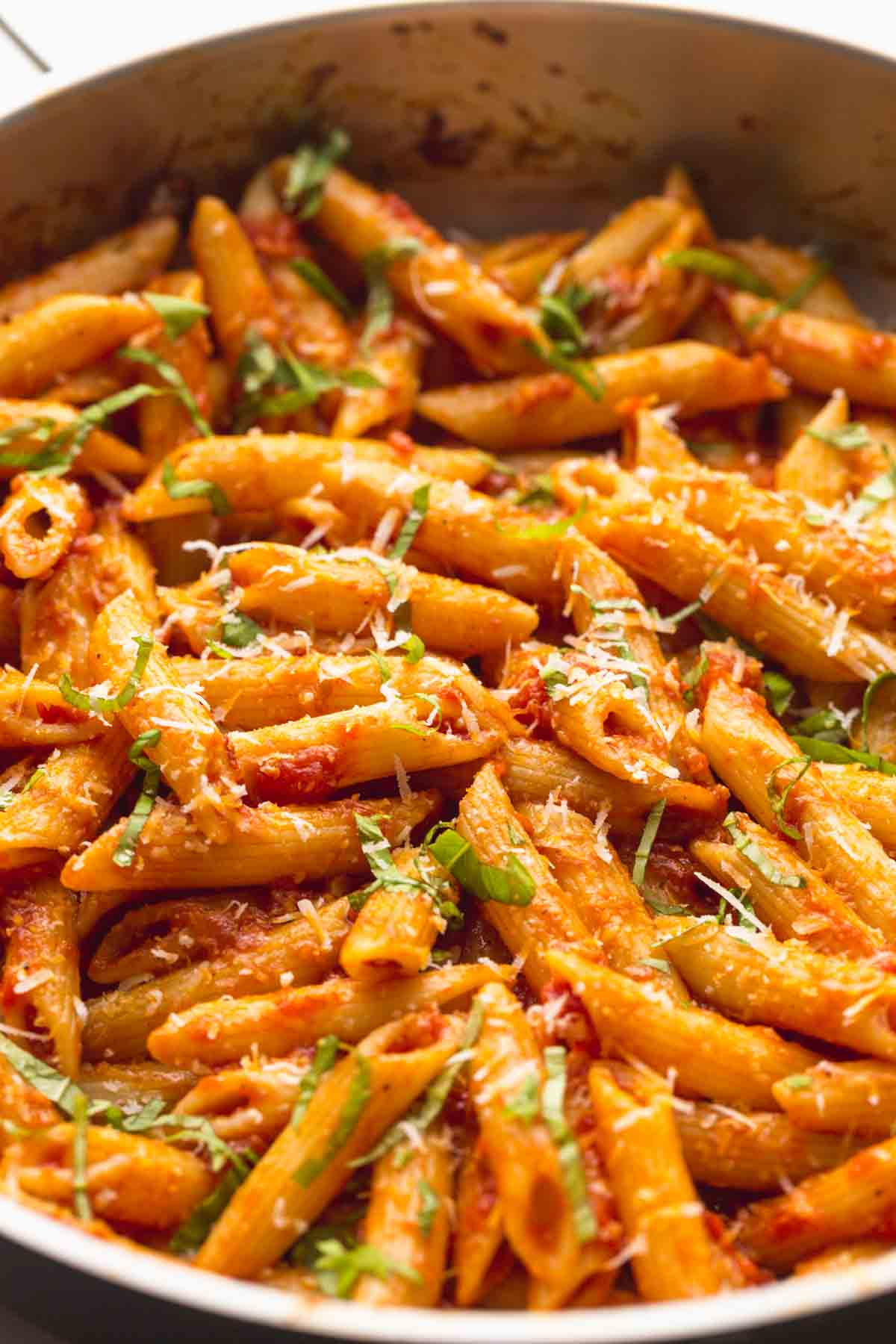 Close up of the pasta in a pan, garnished with parmesan and basil