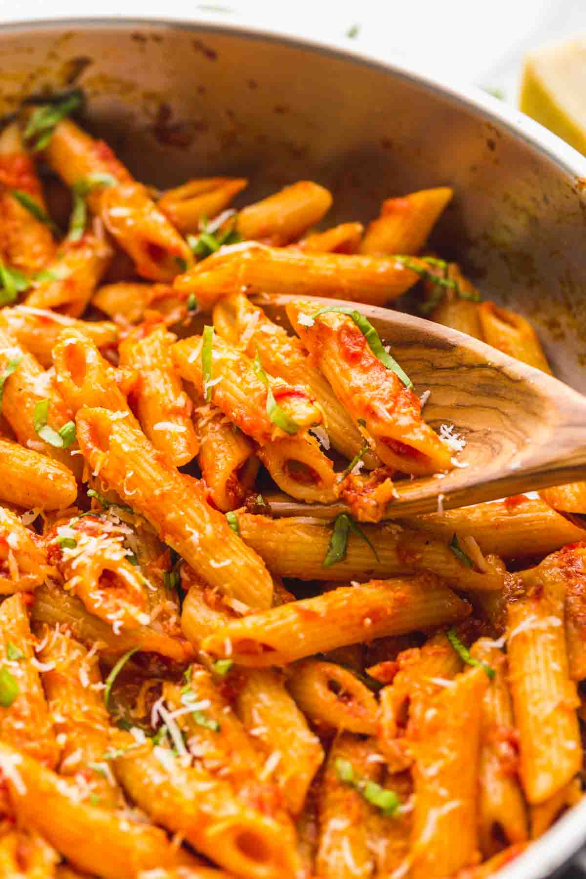 Penne Arrabbiata in a pan, with a wooden serving spoon