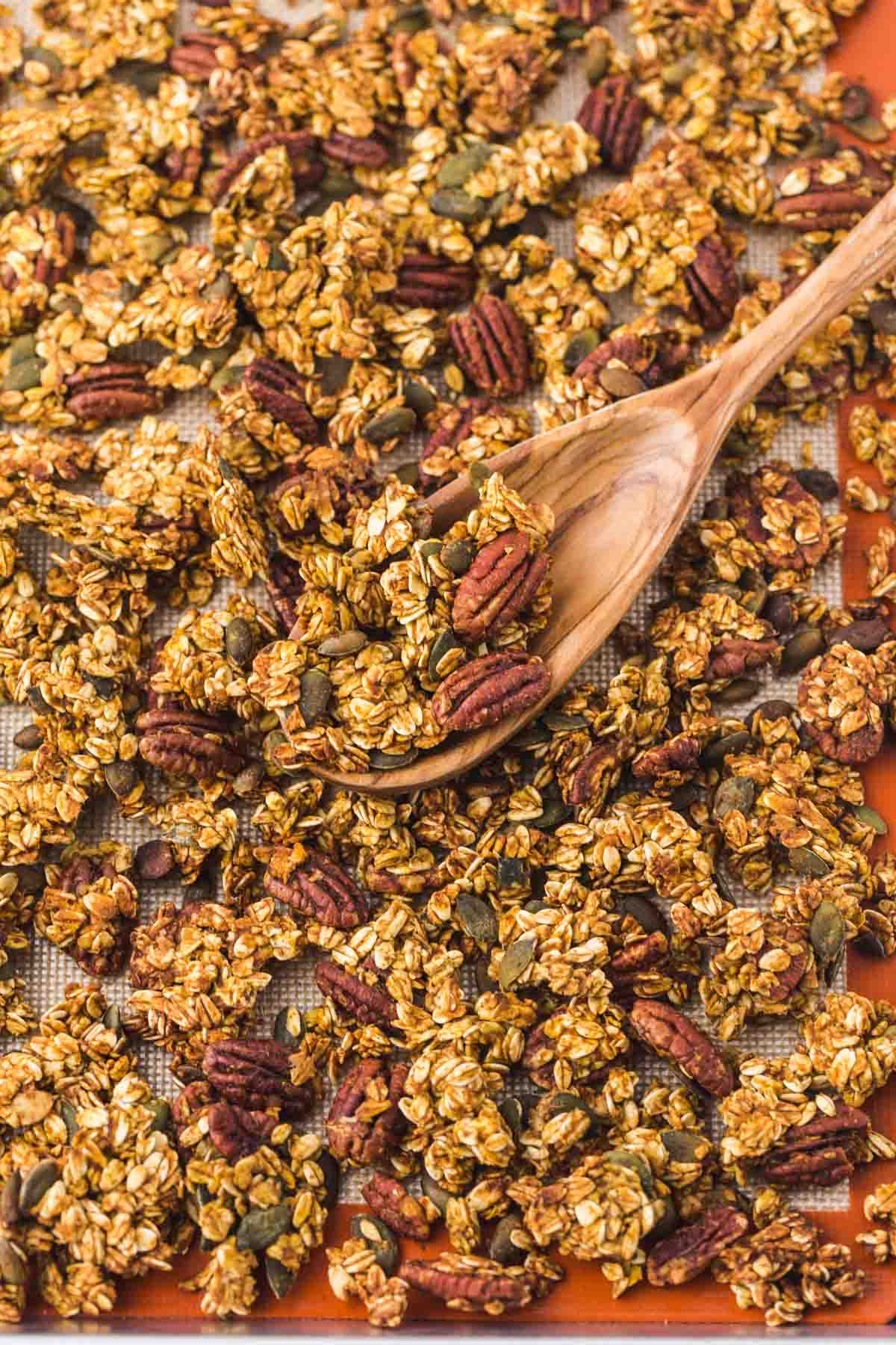 Baked granola on a baking sheet with a wooden spoon