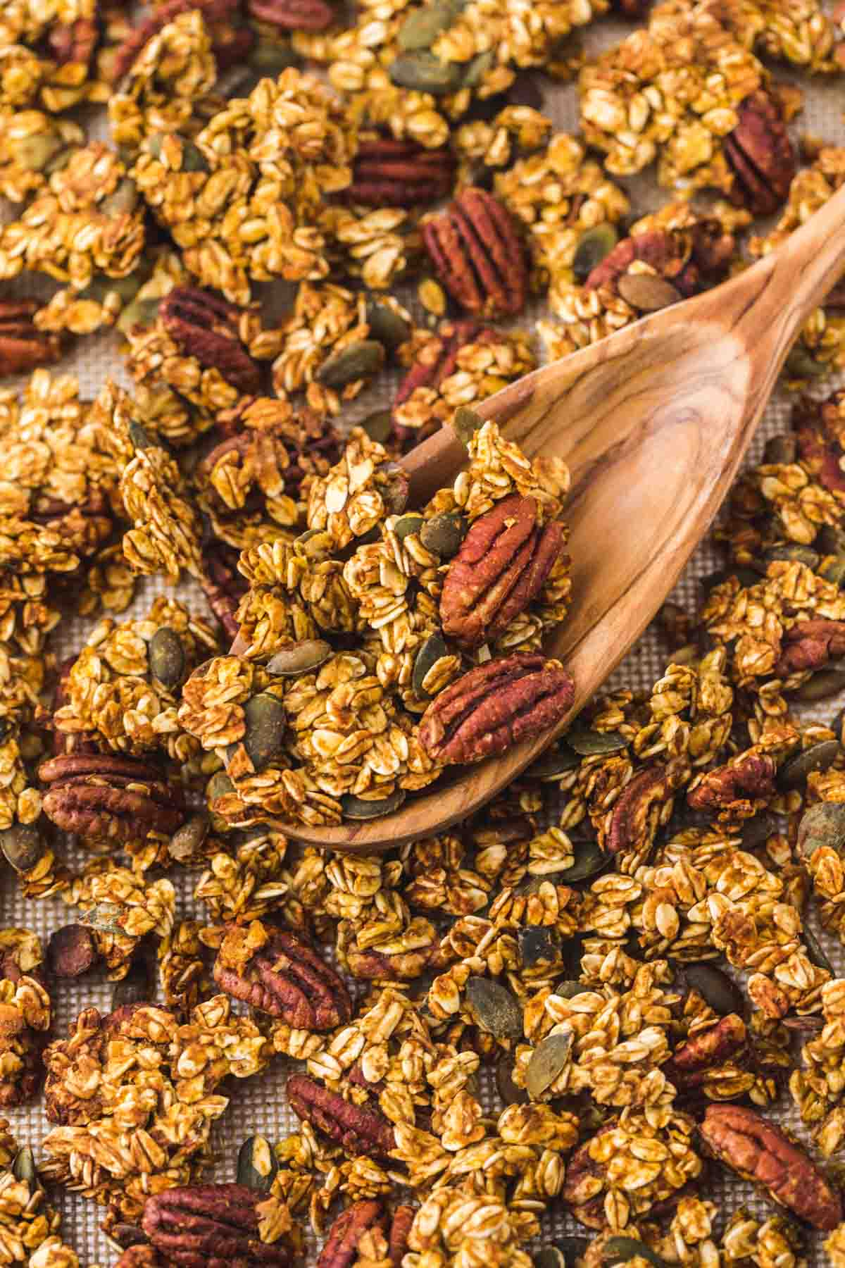 A close up shot of pumpkin granola on a silicone baking mat, with a wooden spoon