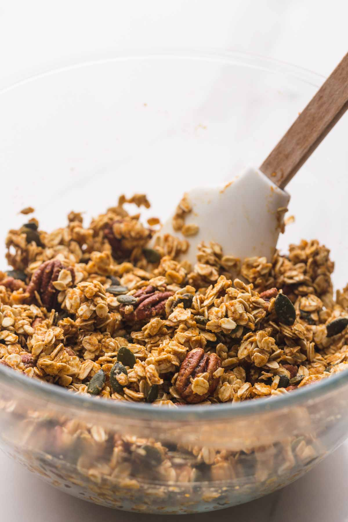 Mixing the granola ingredients with a spatula in a large glass bowl