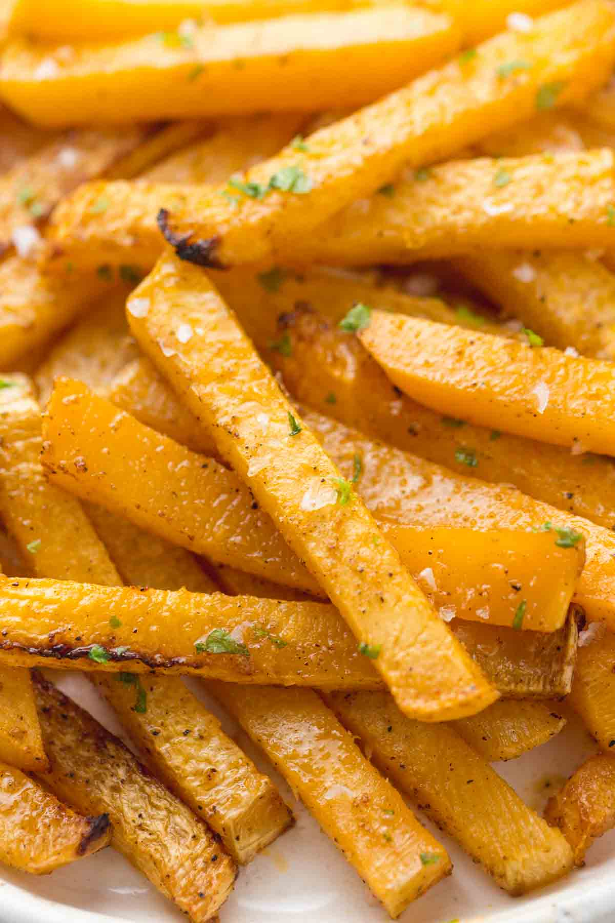 Close up shot of the rubaga fries seasoned with sea salt flakes, and garnished with chopped parsley