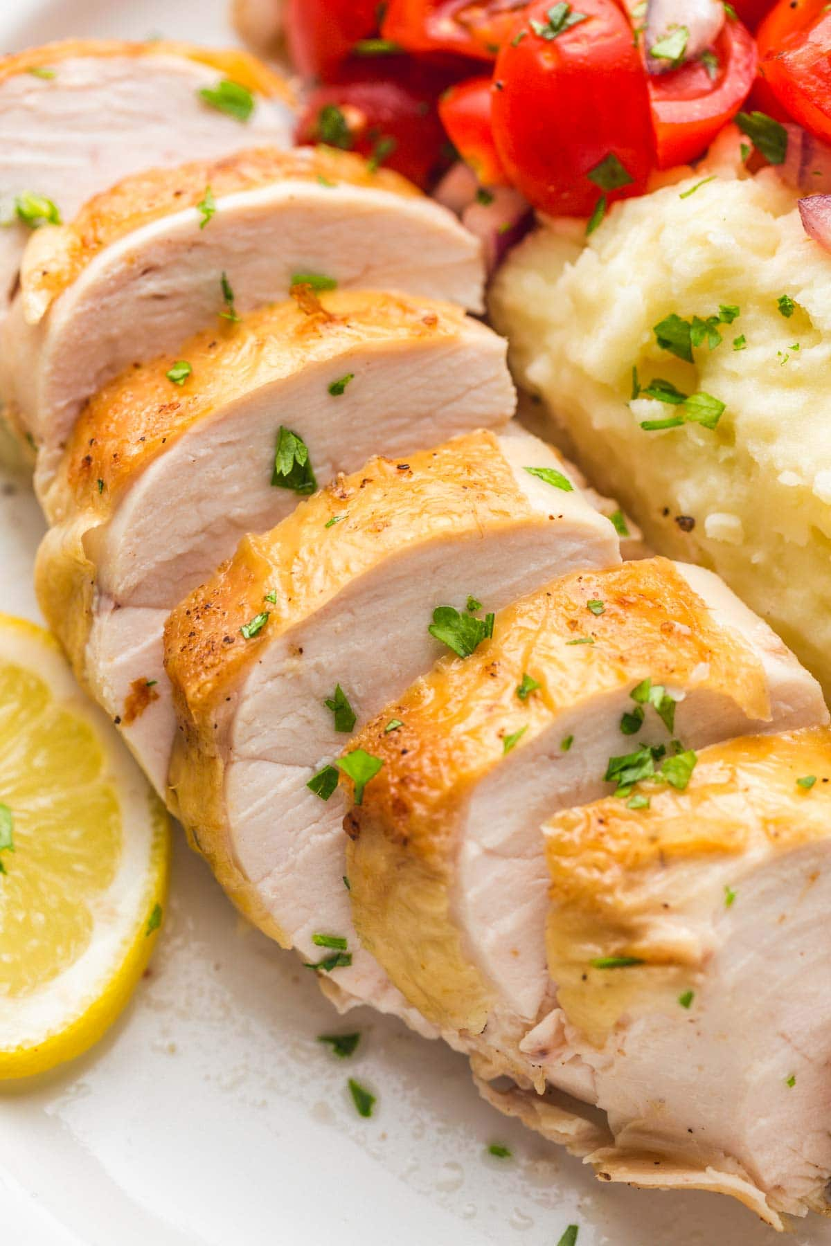 Sliced chicken breast with mashed potatoes and lemon slices.
