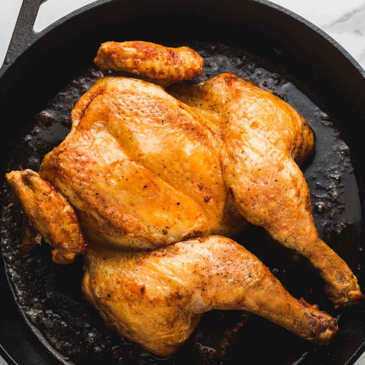 spatchcocked and roasted chicken in a cast iron pan