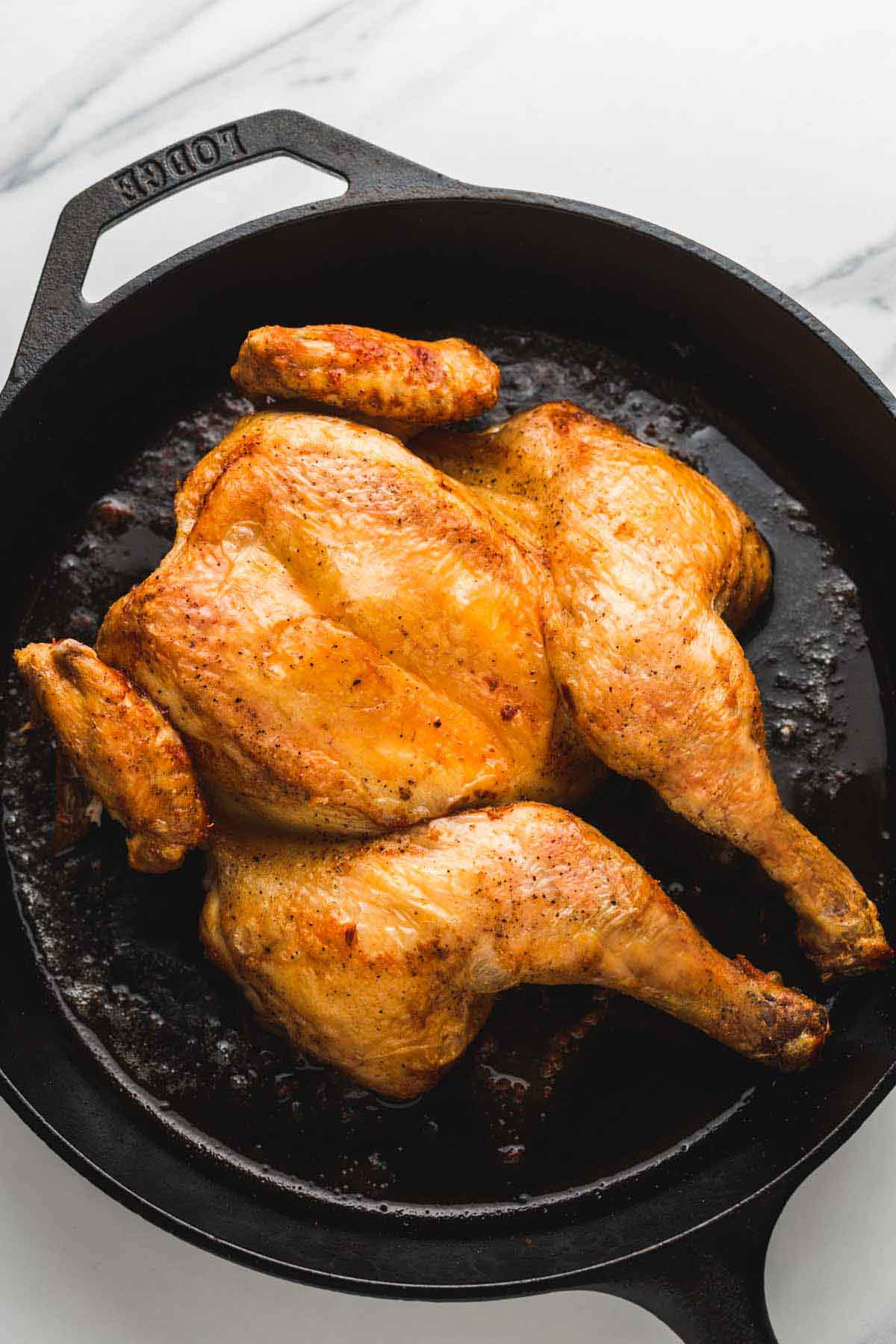 Spatchcock roast chicken in a Lodge cast iron pan