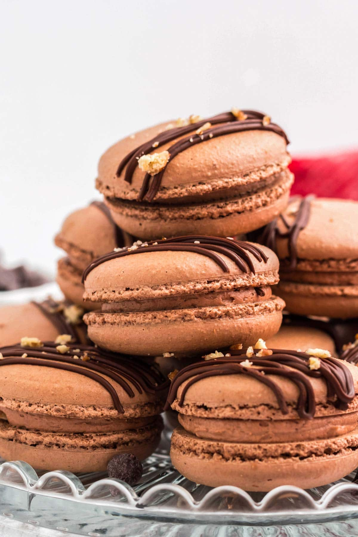 A platter with chocolate macarons stacked.