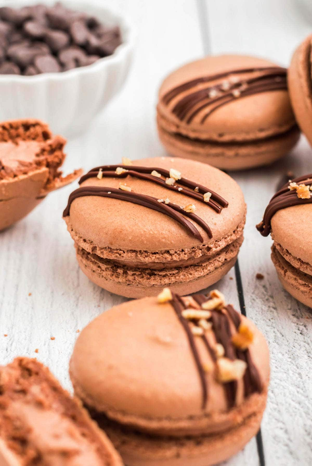 A few chocolate macarons on a white wooden board