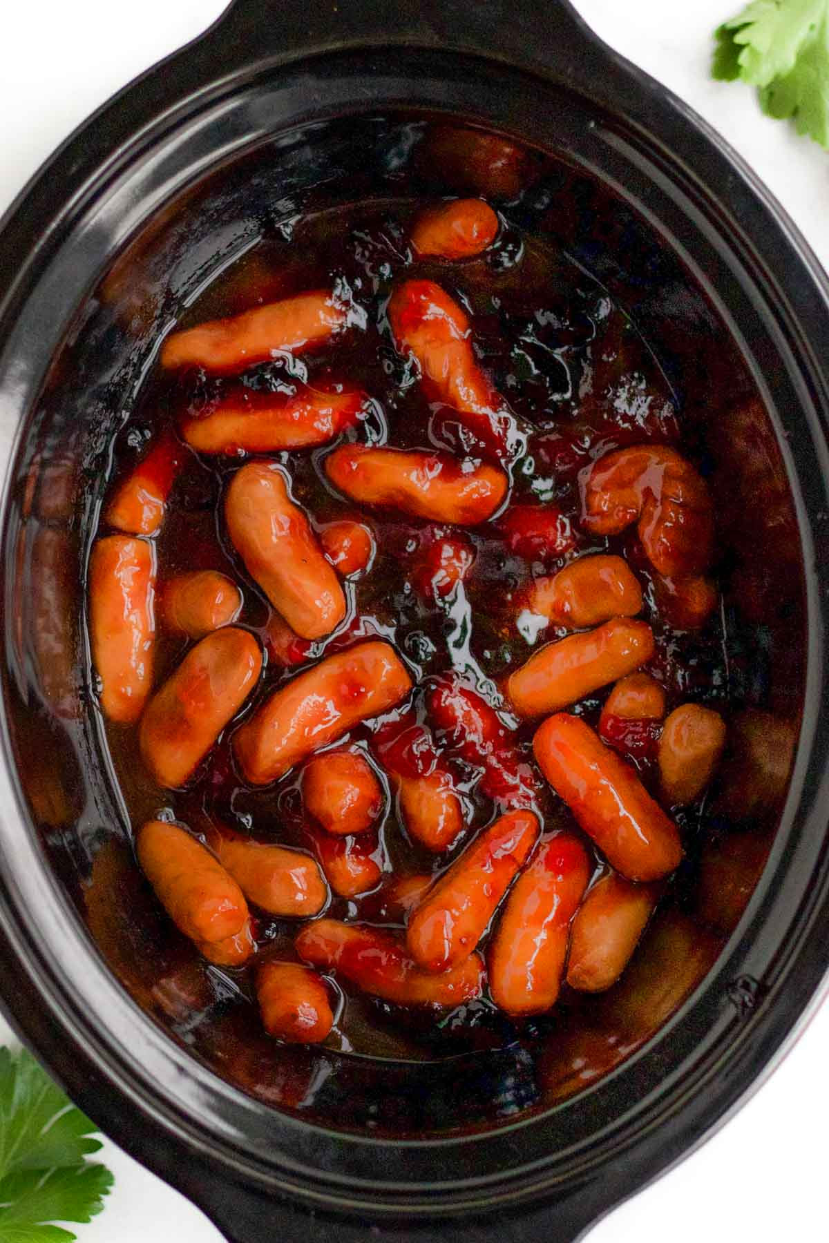 Little smokies with sauce ingredients in the slow cooker before cooking.