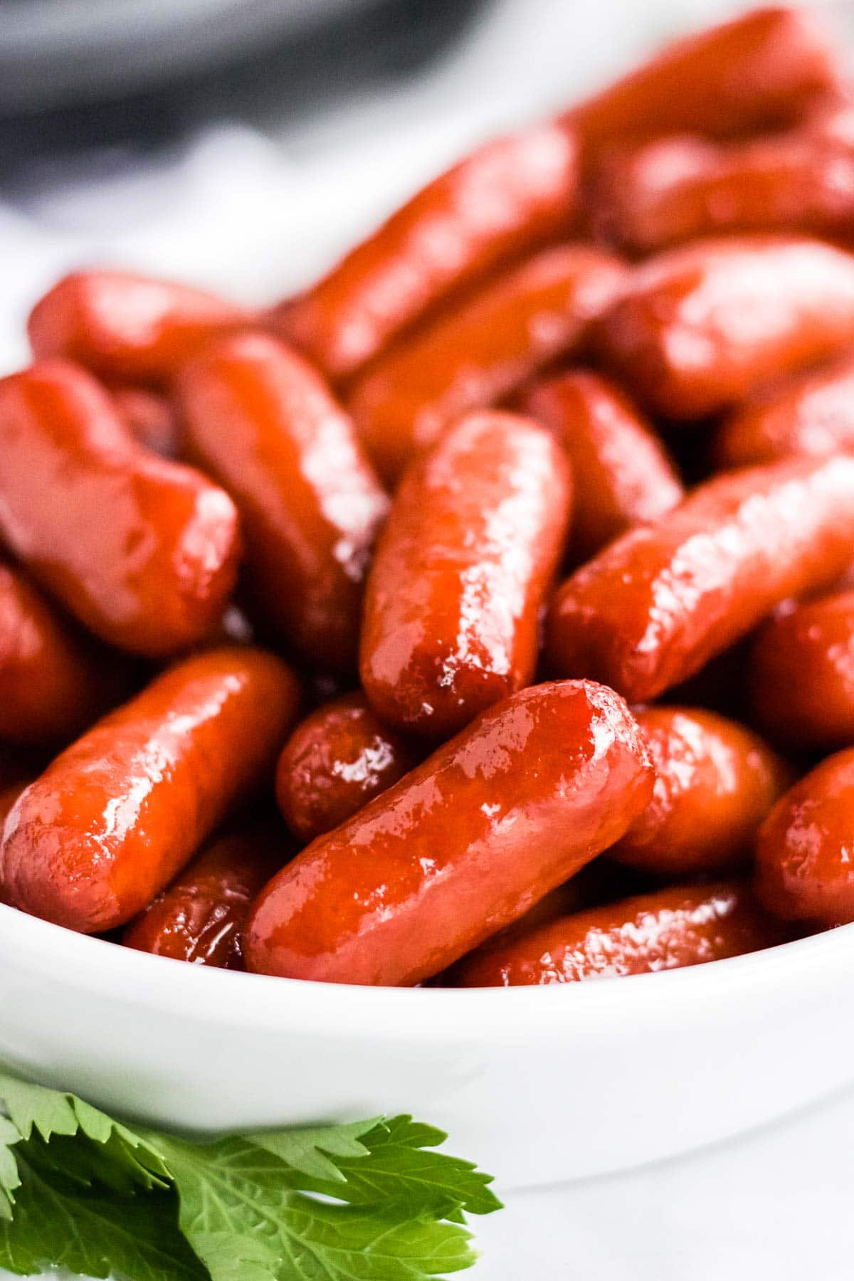 Close up shot of little smokies served in a white bowl