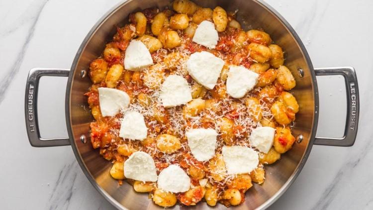 gnocchi in tomato sauce topped with mozzarella and parmesan