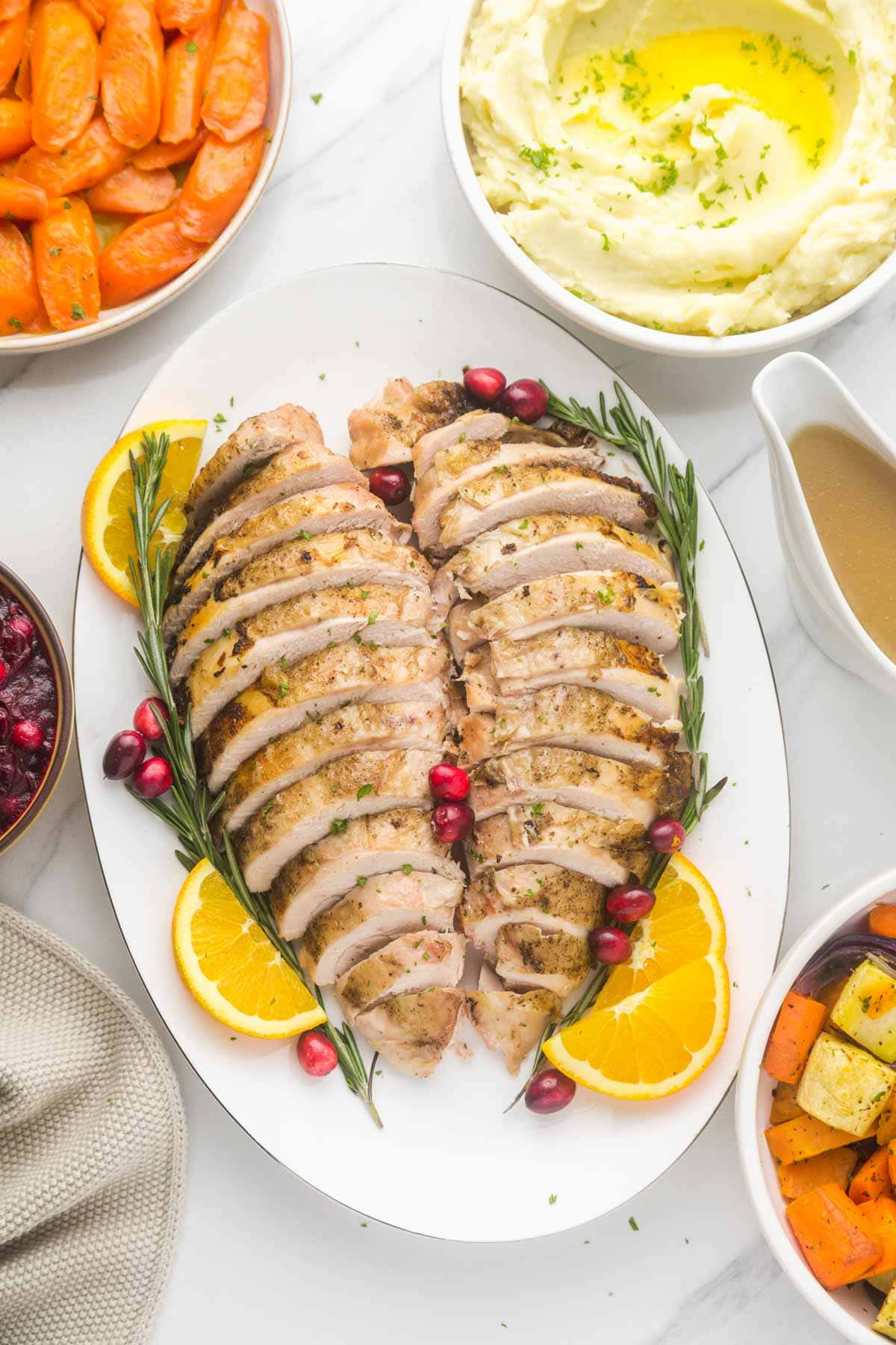 A turkey breast sliced and served on a platter with orange sliced, rosemary sprigs, and fresh cranberries