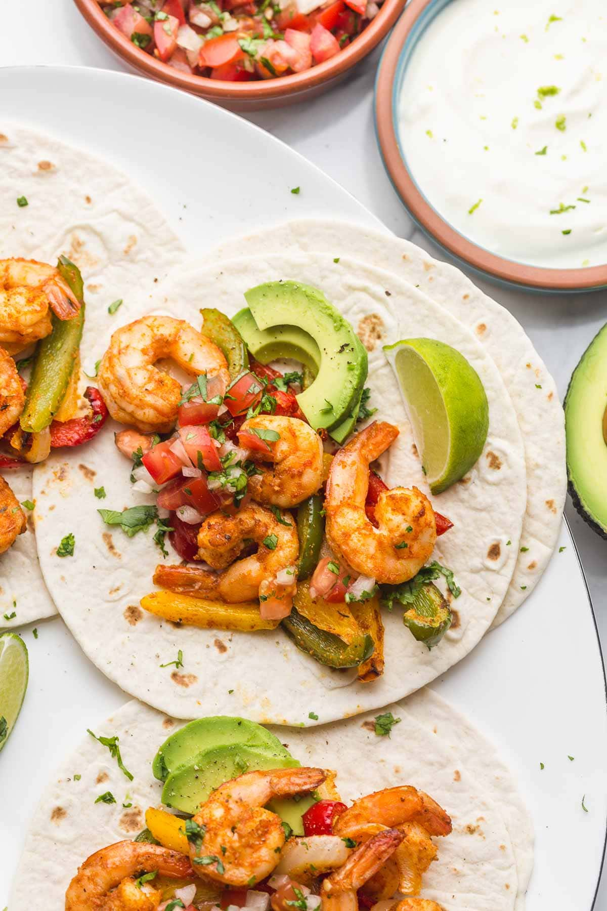 Overhead shot of shrimp fajitas on tortillas with fresh wedges of lime and sliced avocado