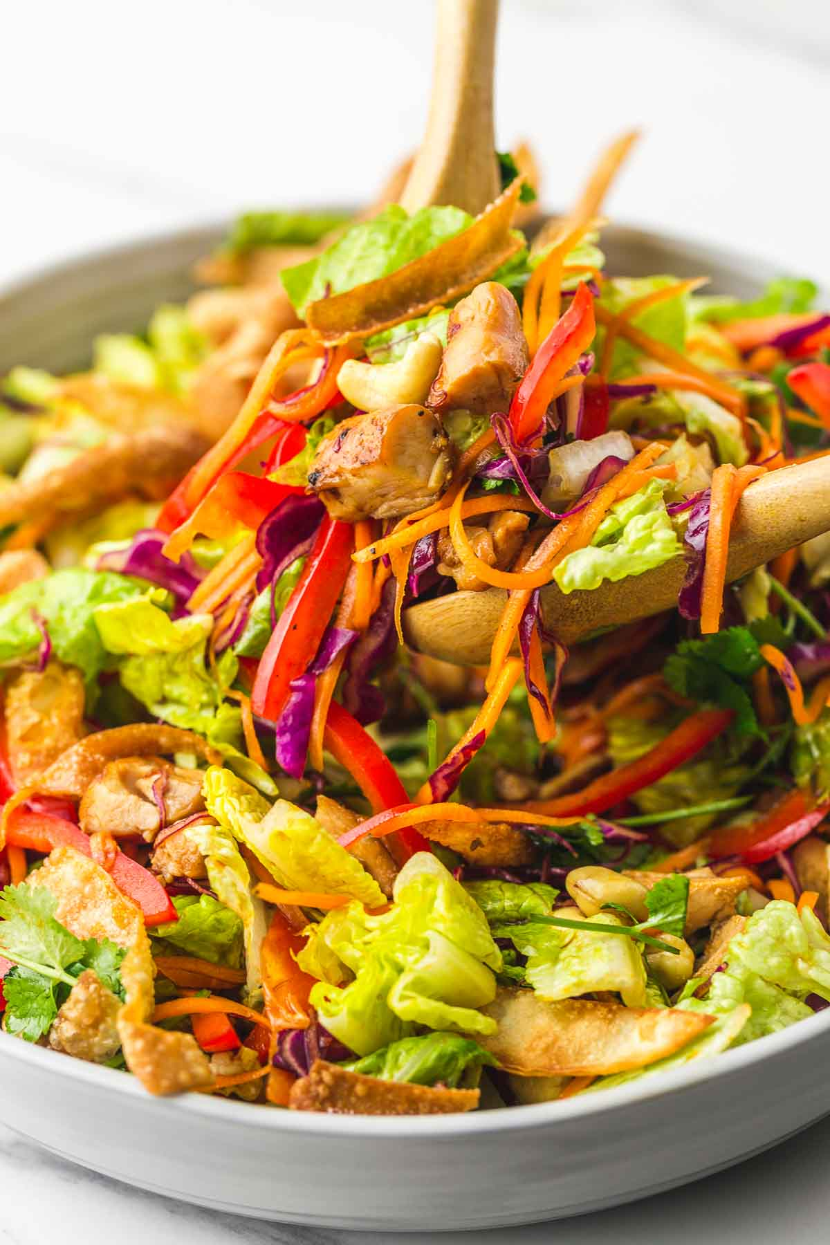 Angle shot of the Asian chicken salad, and serving spoons holding a portion of the salad to be served.
