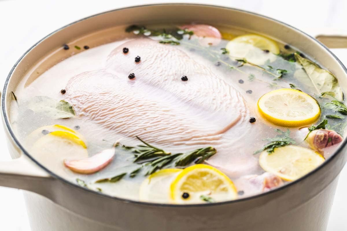 A whole raw chicken submerged in brine, fresh lemon slices, herbs, garlic, and peppercorns.
