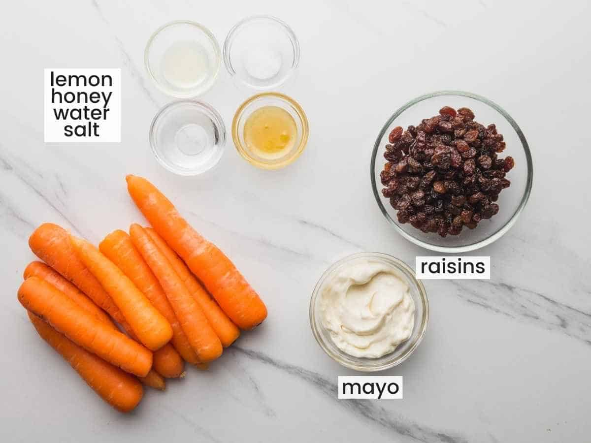 Overhead shot of ingredients needed to make a carrot salad including carrots, raisins, mayo, honey, lemon juice, water, and salt.