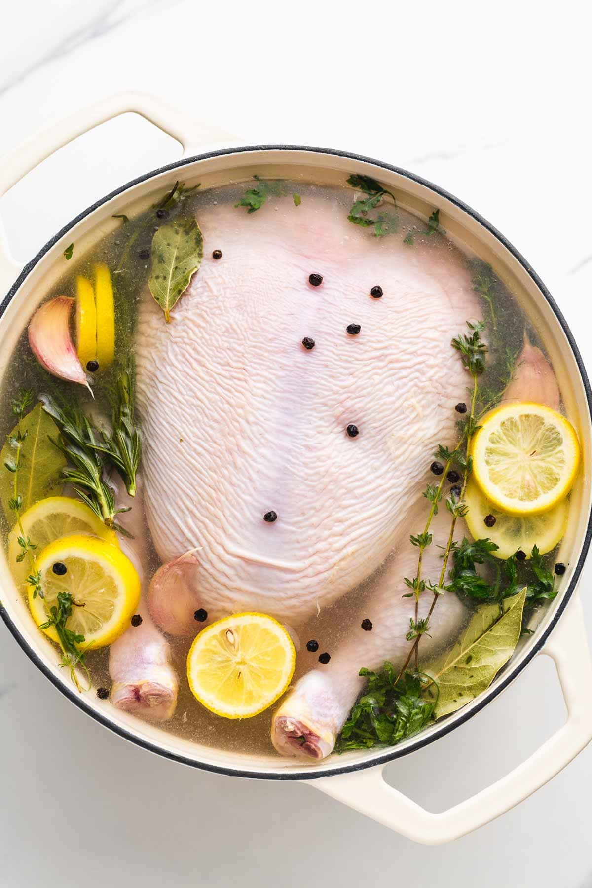 A whole chicken being brined in a large pot with slices of lemon, herbs, garlic cloves, and black peppercorns.