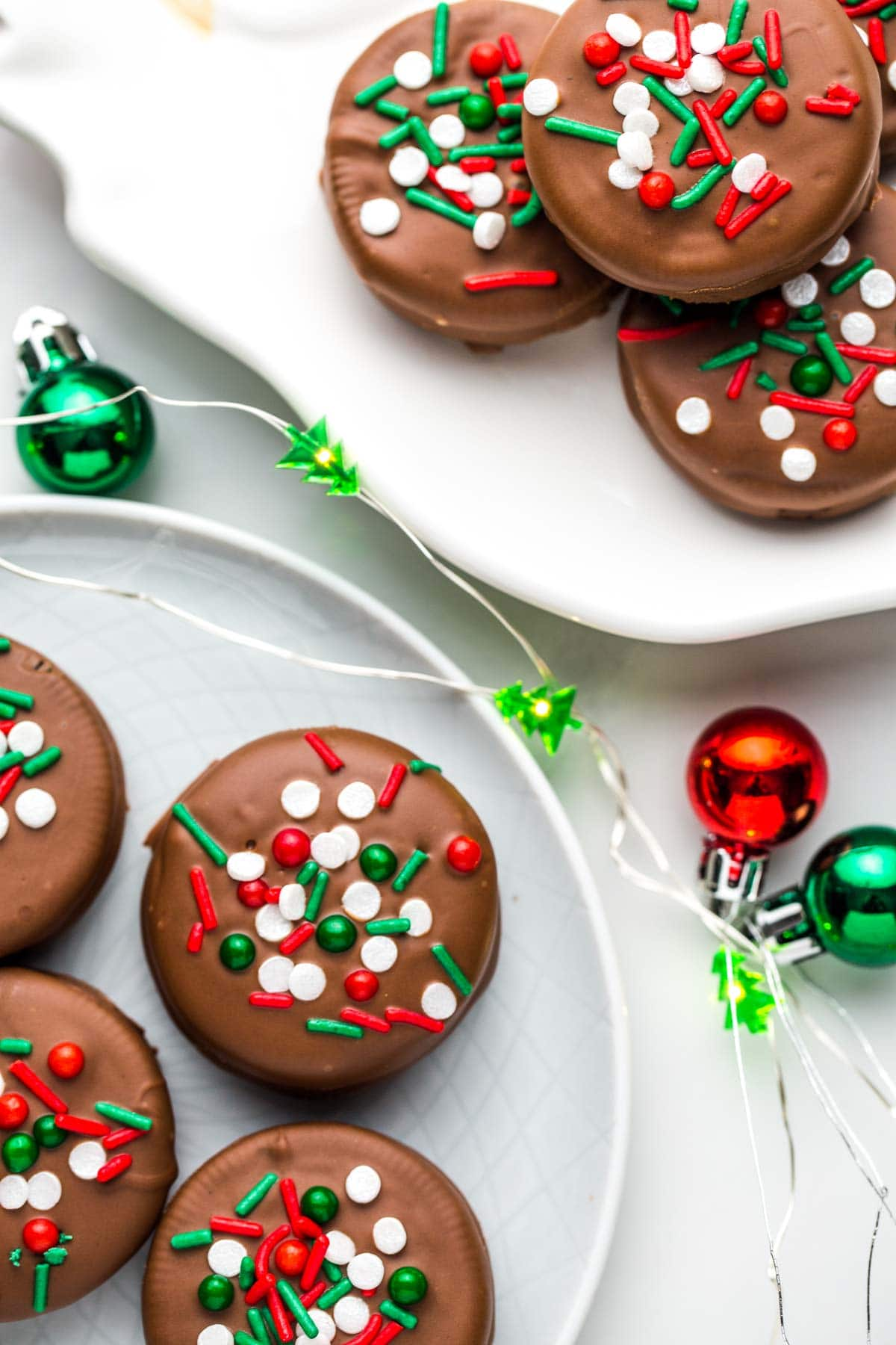 Overhead shot of 2 plates with Chocolate Covered Oreos with Christmas ornaments and lights.