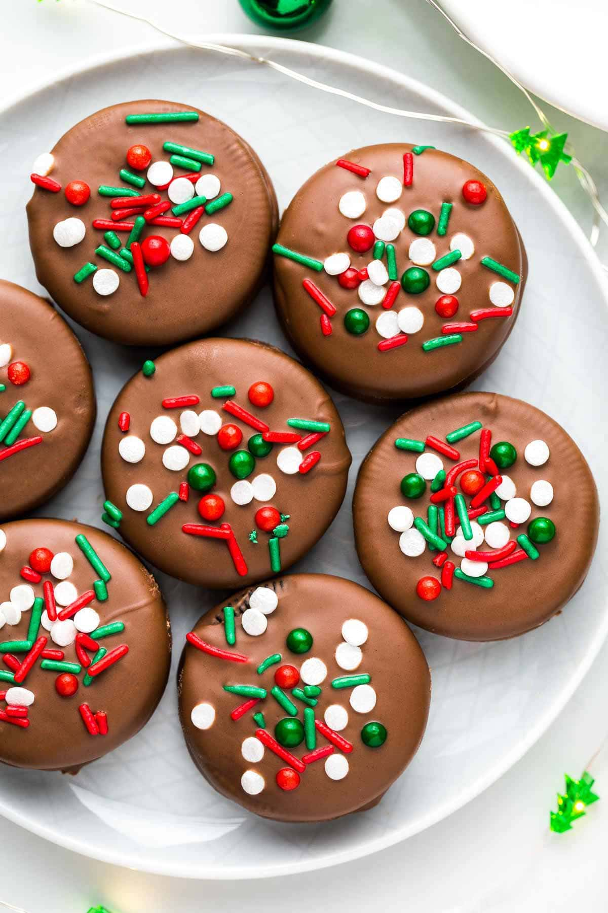 Overhead shot of Chocolate Covered Oreos on a plate with Christmas ornaments and lights.