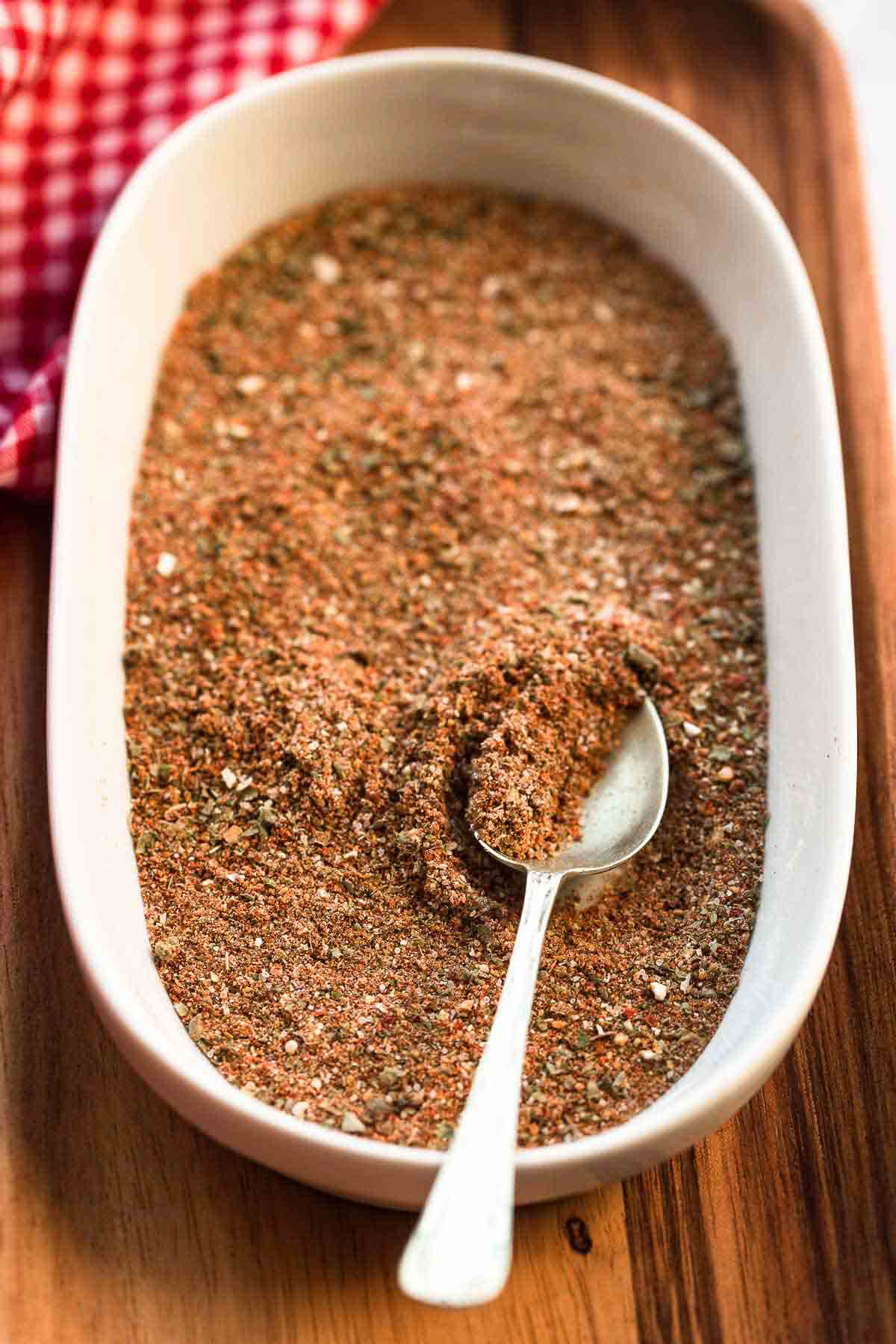 Taco seasoning in a bowl with a teaspoon, placed on a wooden board