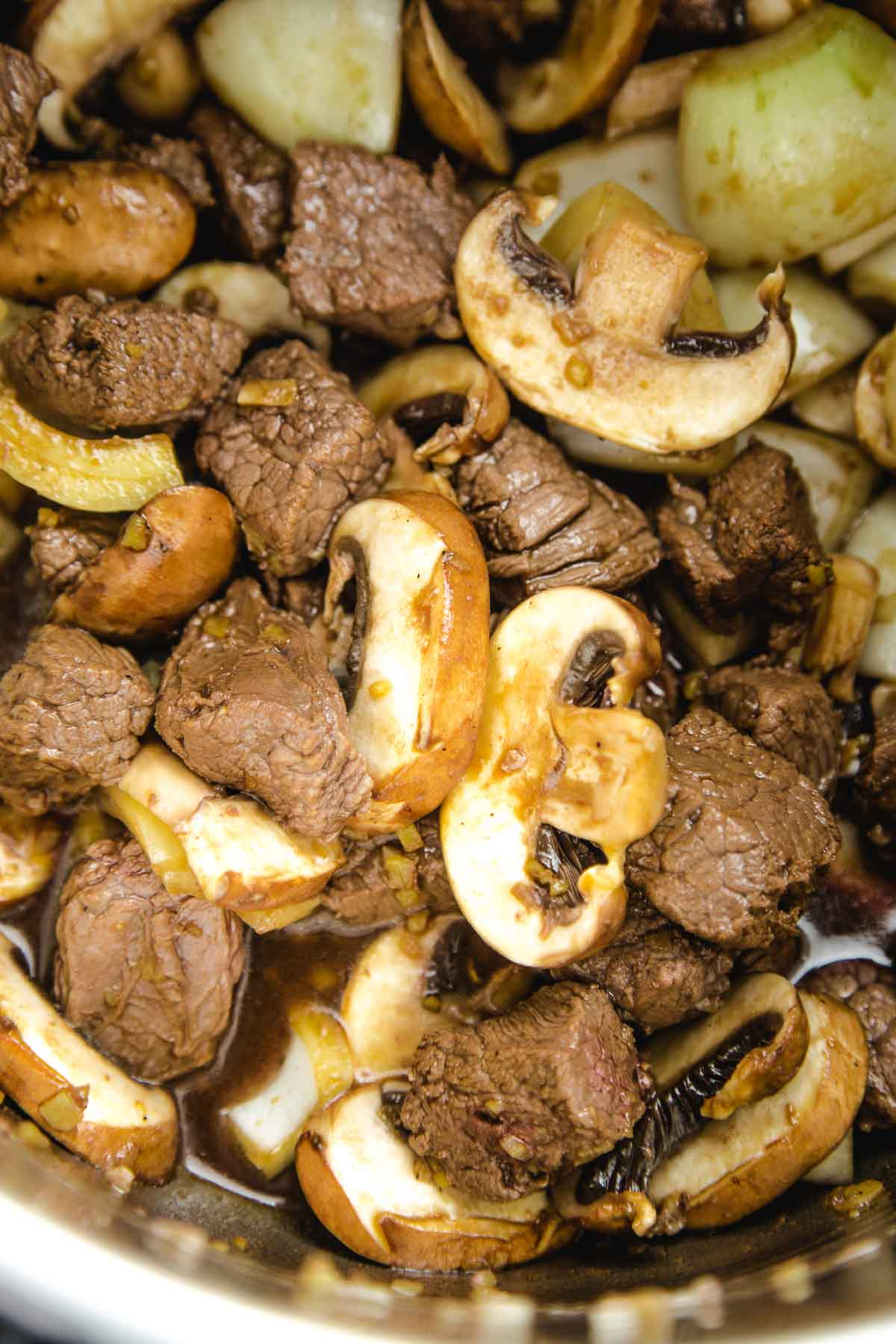 seared steak and raw mushrooms in soy sauce - a close up shot