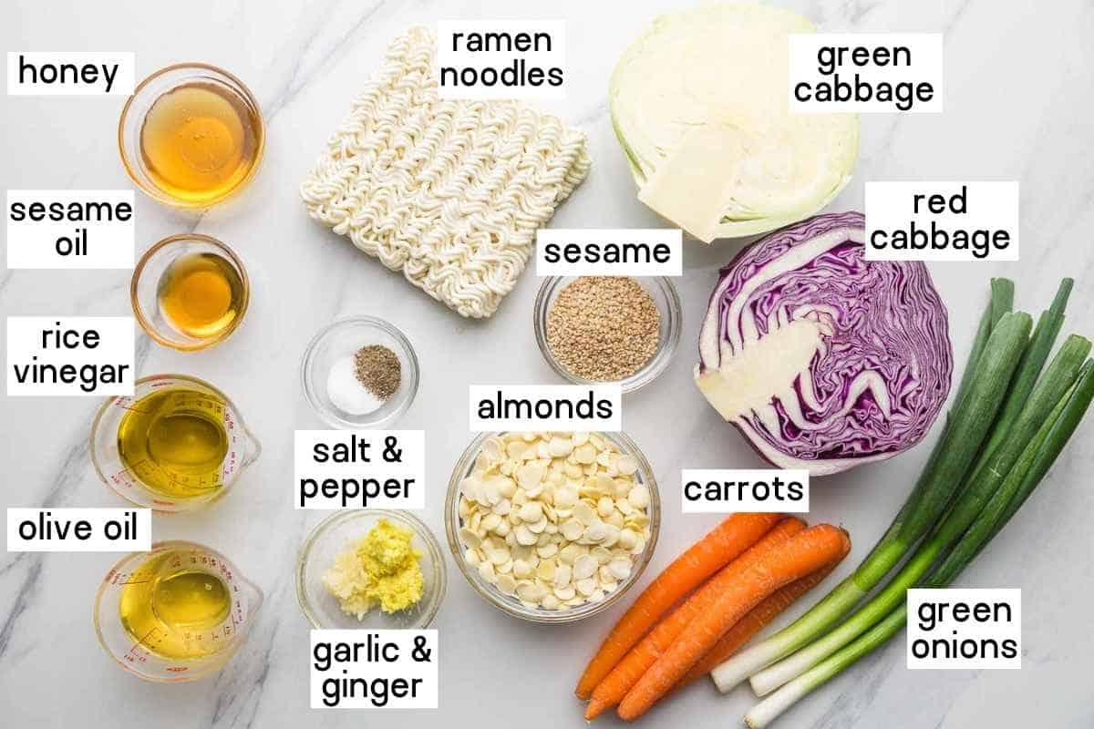 Ingredients needed to make the salad including ramen noodles, cabbage, red onion, carrots, almonds, garlic, ginger, and dressing ingredients.