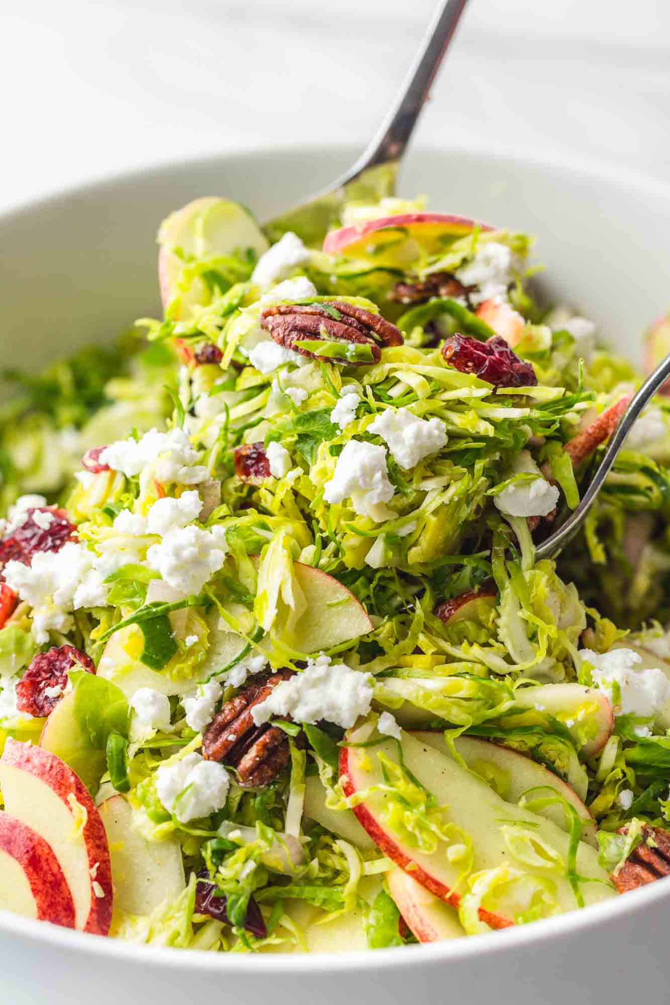 Tossing Shaved Brussels Sprout Salad using salad servers