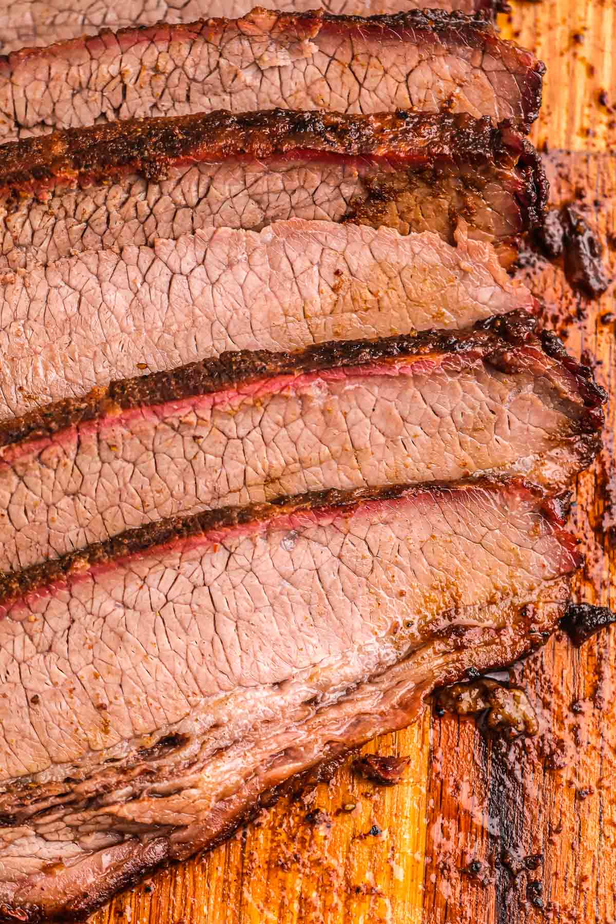 5 slices of juicy smoked brisket on a wooden cutting board.