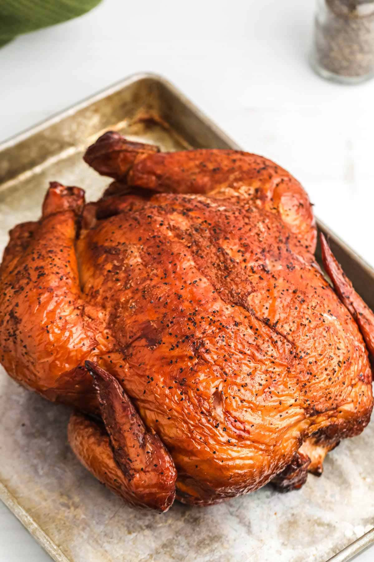 A whole smoked chicken placed ona. tray