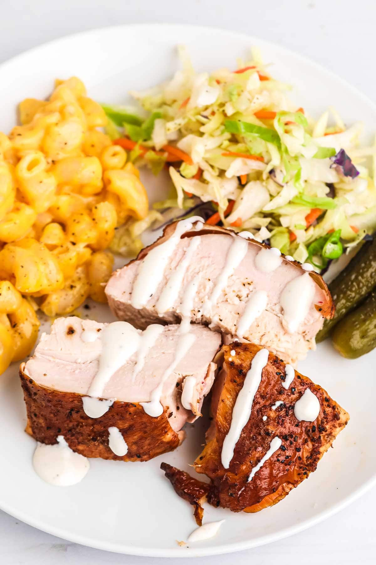 Sliced chicken breast served on a plate drizzled with alabama white sauce, served with coleslaw and mac and cheese.