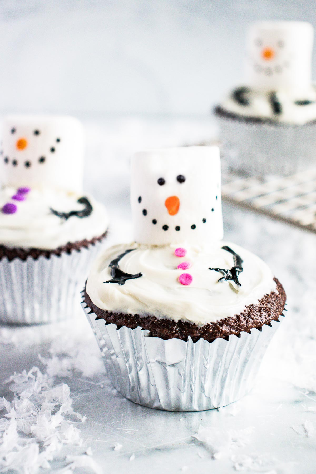 Snowman cupcakes on a marble countertop