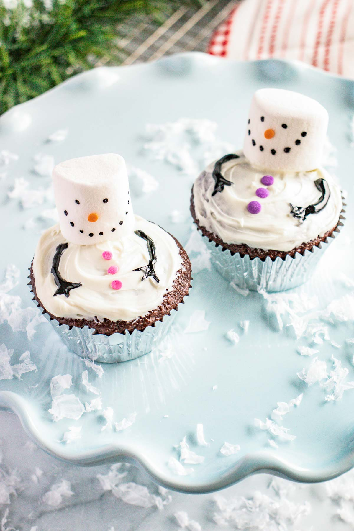 2 snowman cupcakes on a cake stand