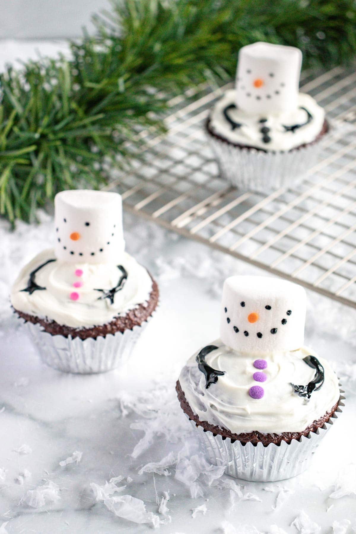 3 snowman cupcakes on a marble countertop