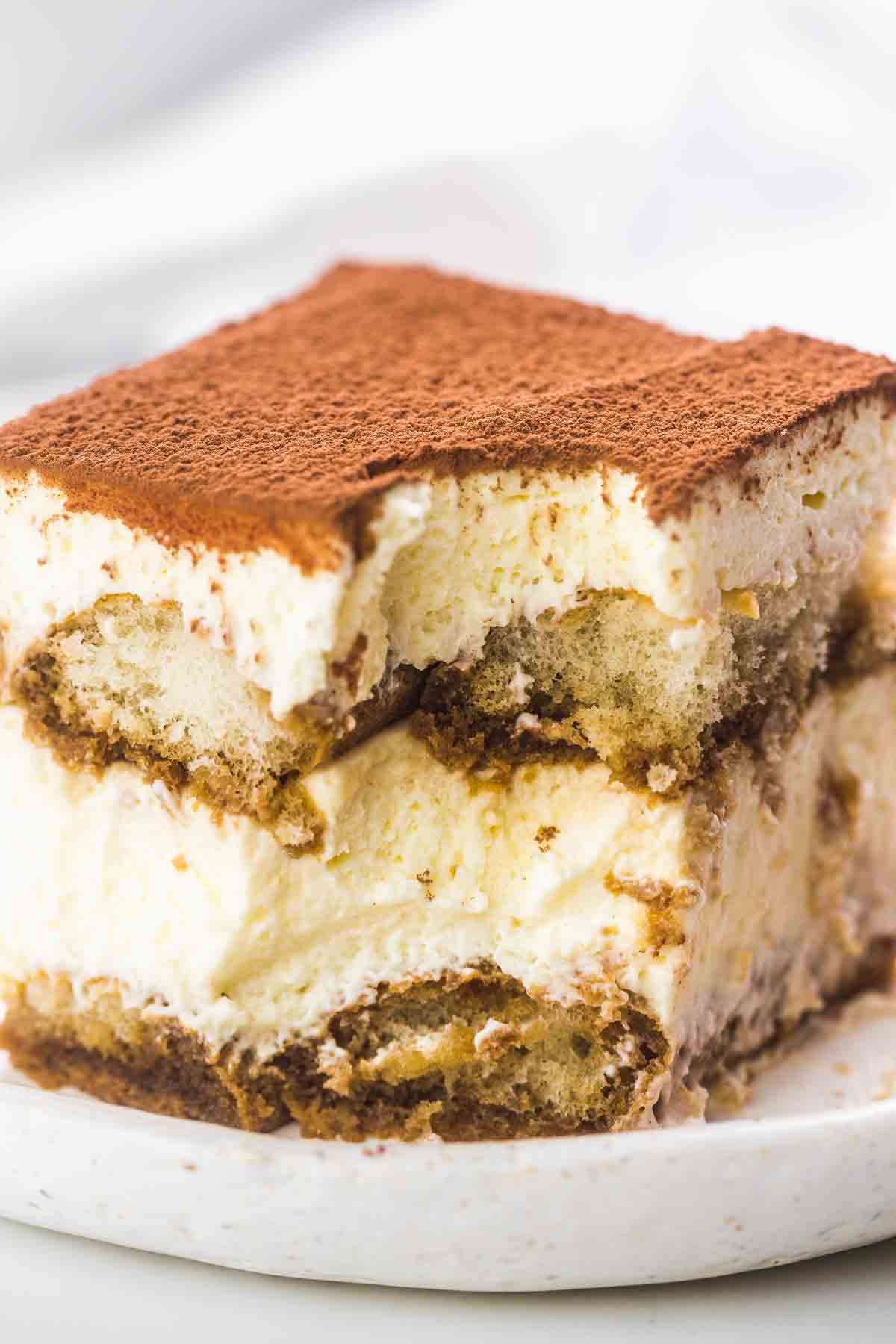 A slice of tiramisu served on a white plate, showing the layers of the cake.