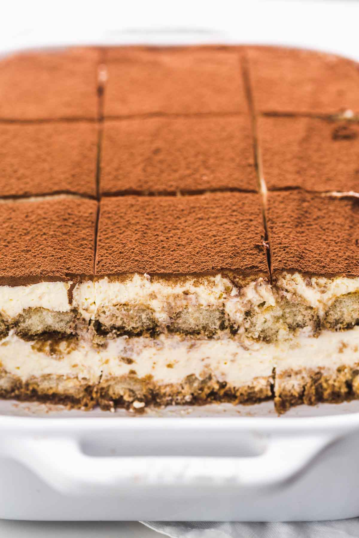 Close up shot of the tiramisu in a casserole dish showing the inside layers of the ladyfingers with the cream and espresso