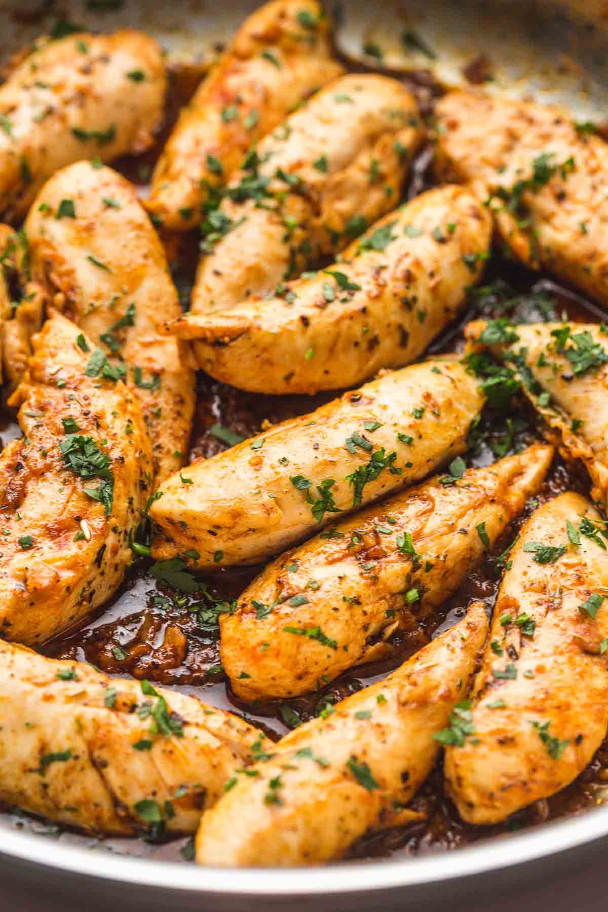 Close up shot of chicken tenders cooked in a sauce with chopped parsley